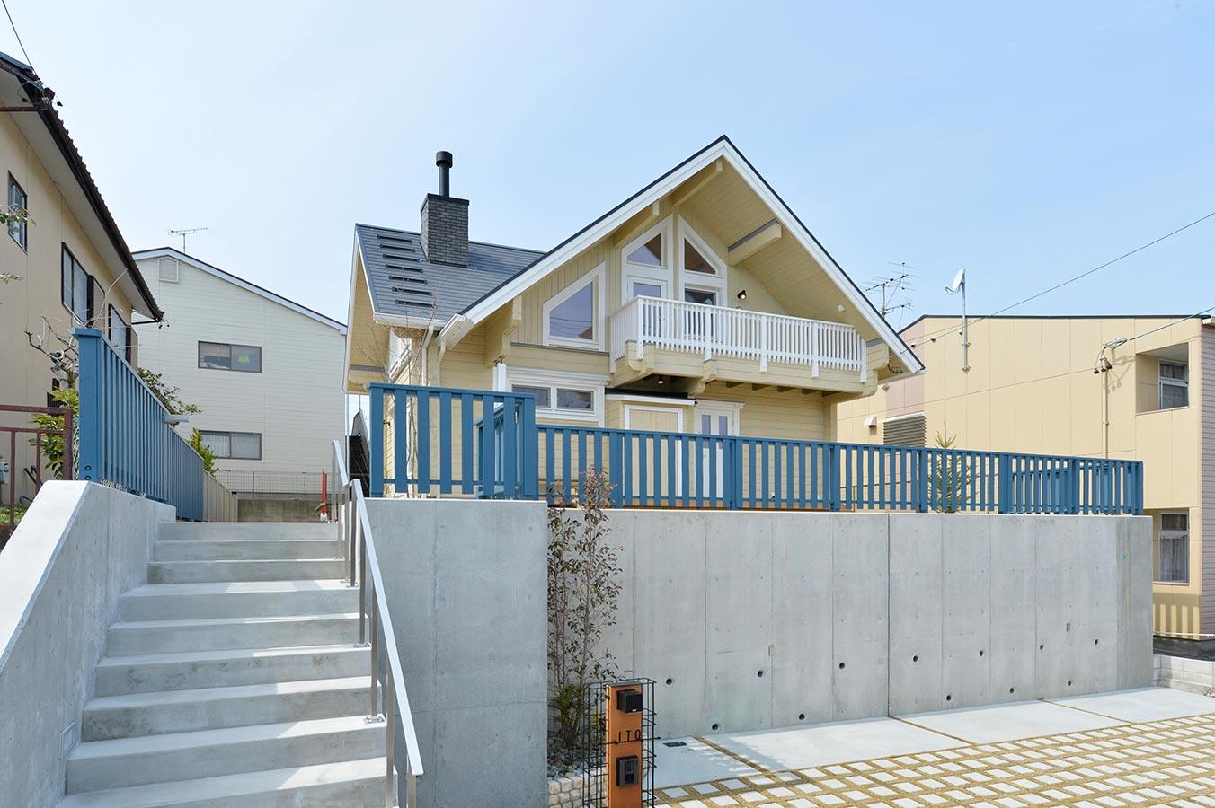 鮮やかに映えるブルーの柵の奥に、目を引く大屋根のログハウス
