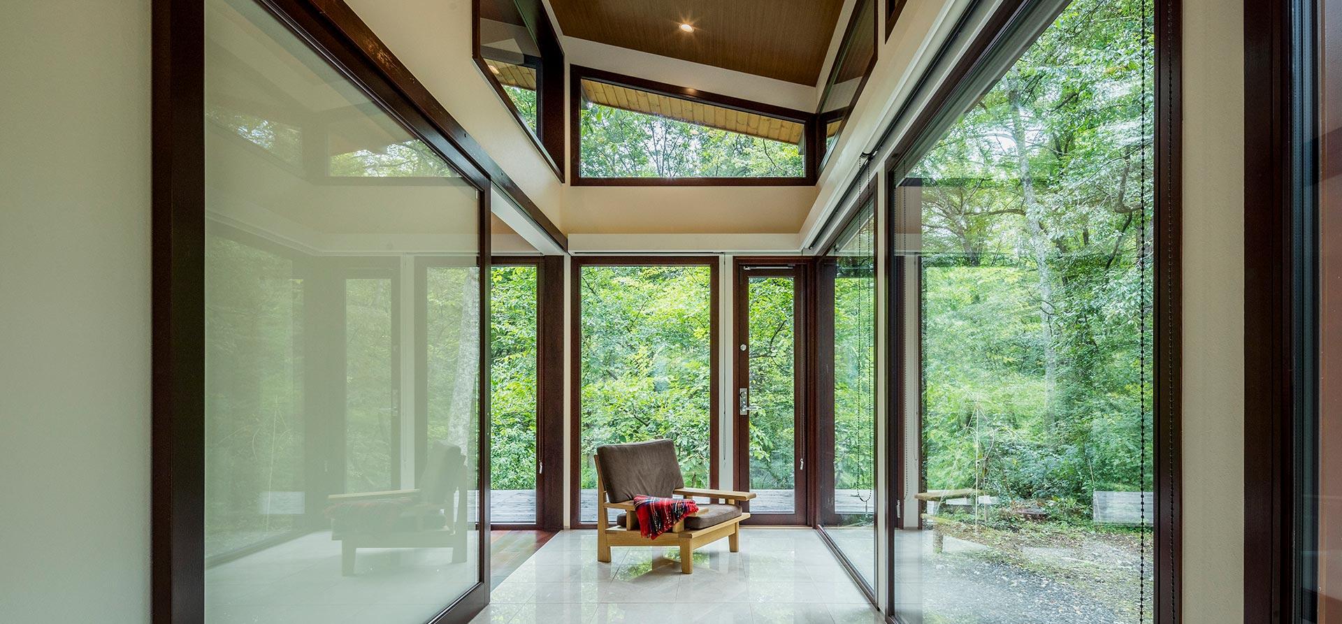 ガラスで覆われたサンルーム。リビングと隔てる室内ドアは、大きい一枚のガラス引き戸を設置
