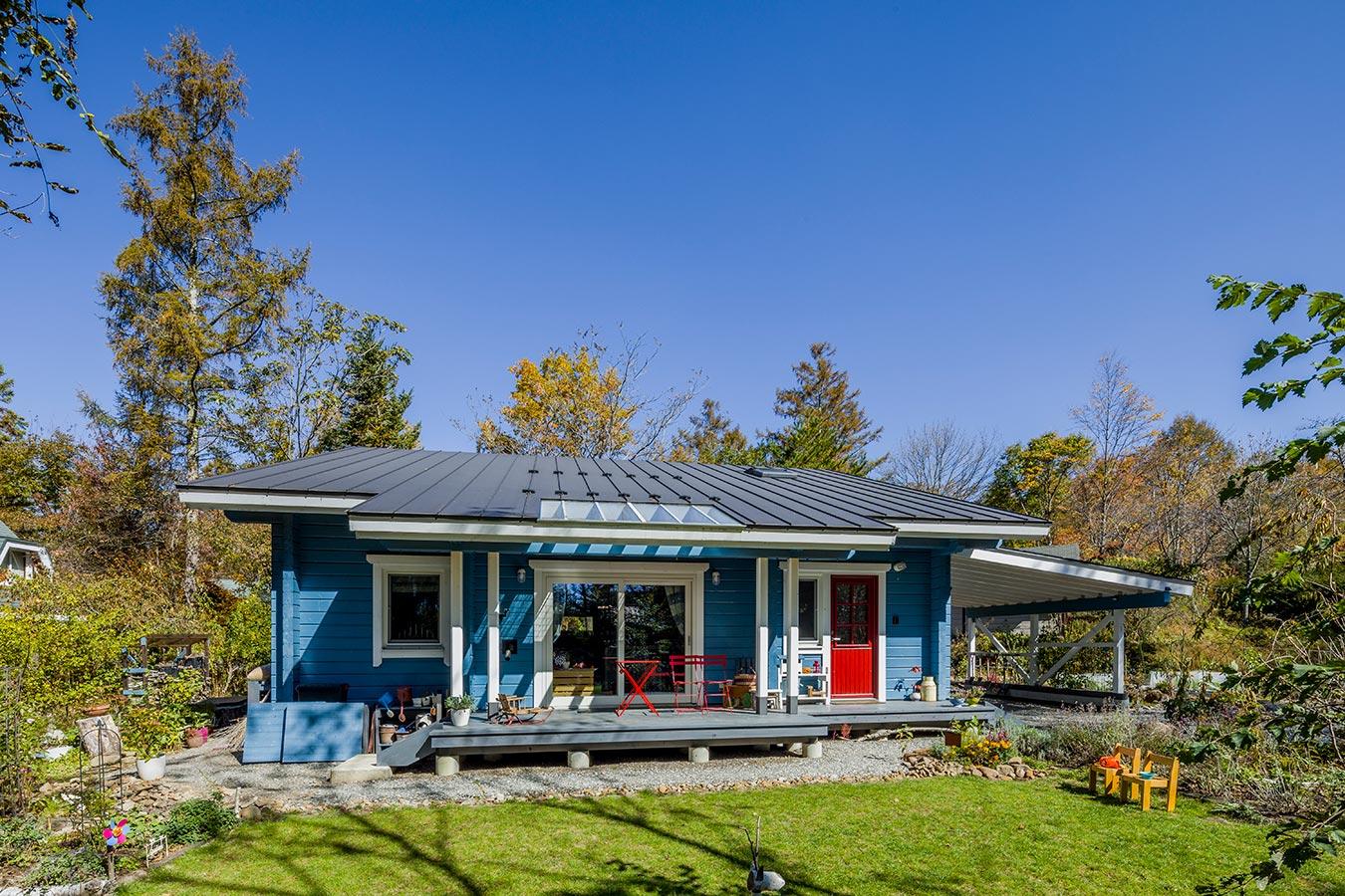 芝生の緑と建物のブルー、エントランスドアの赤が鮮やかなコントラストを描く片流れ屋根のシャープな外観。