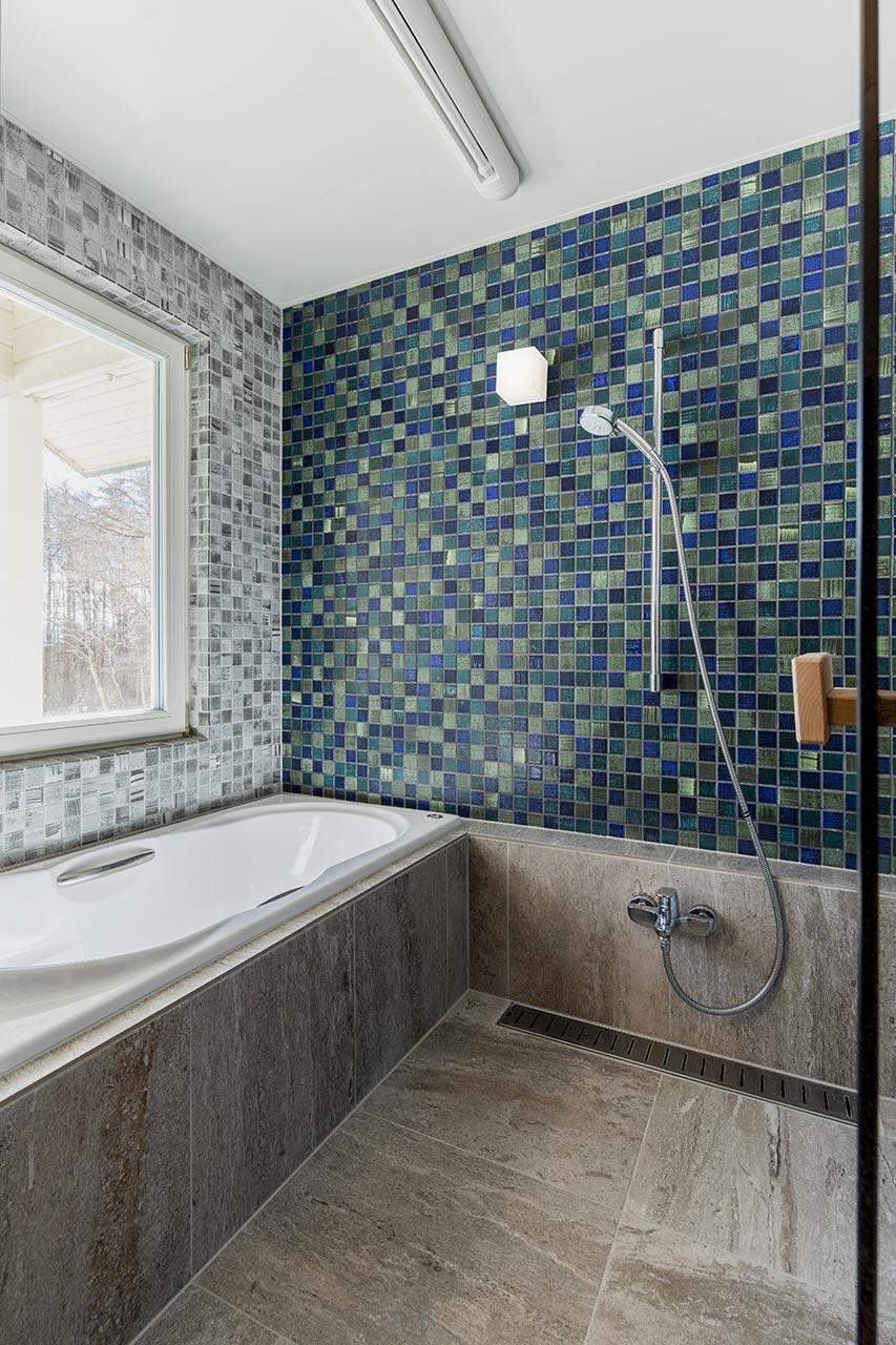 洗面台と連続するタイル壁で統一感をもたせたバスルーム