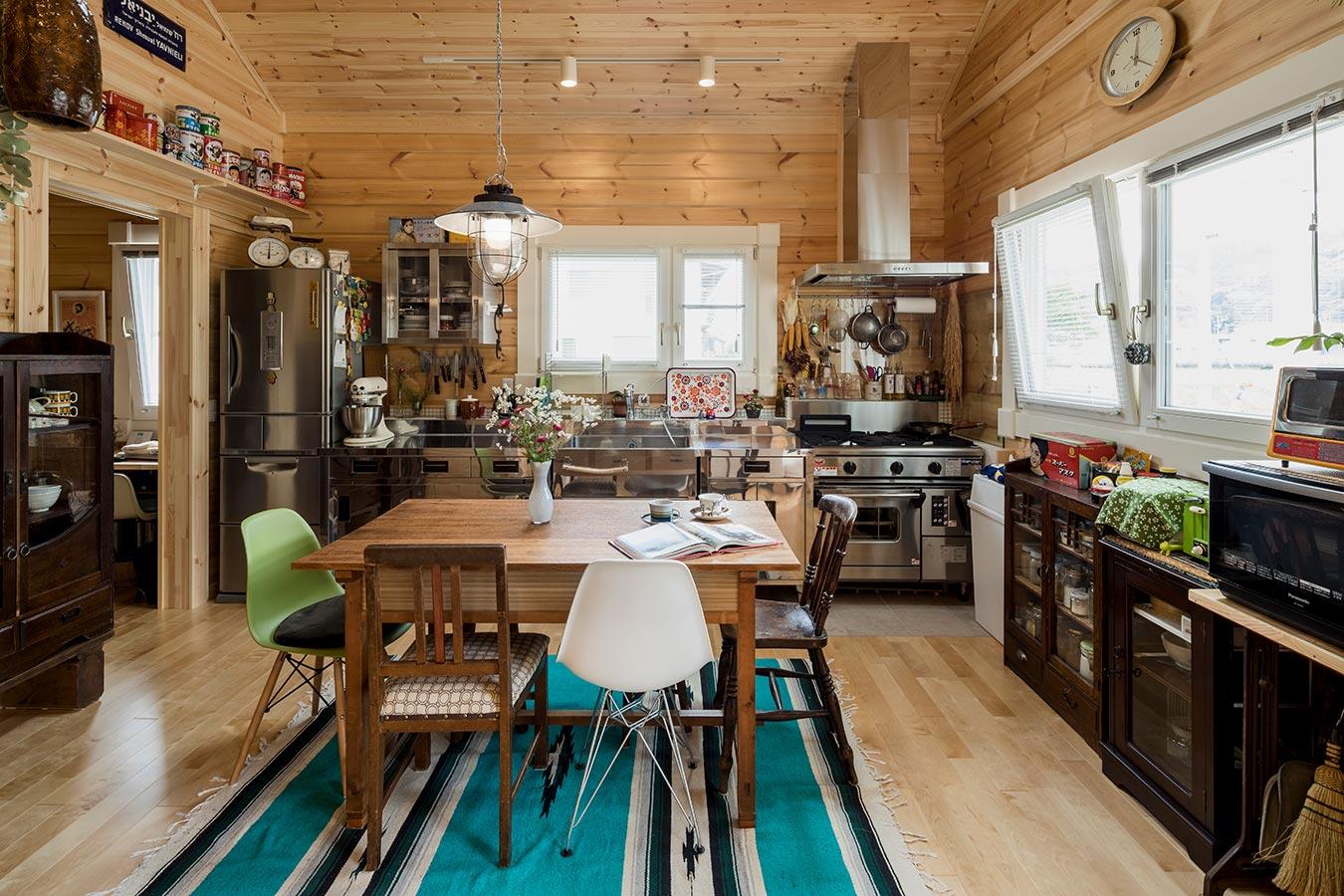 業務用キャビネットや古い茶箪笥などがにぎやかに並ぶキッチン。左奥には家事と収納スペースを備えています。