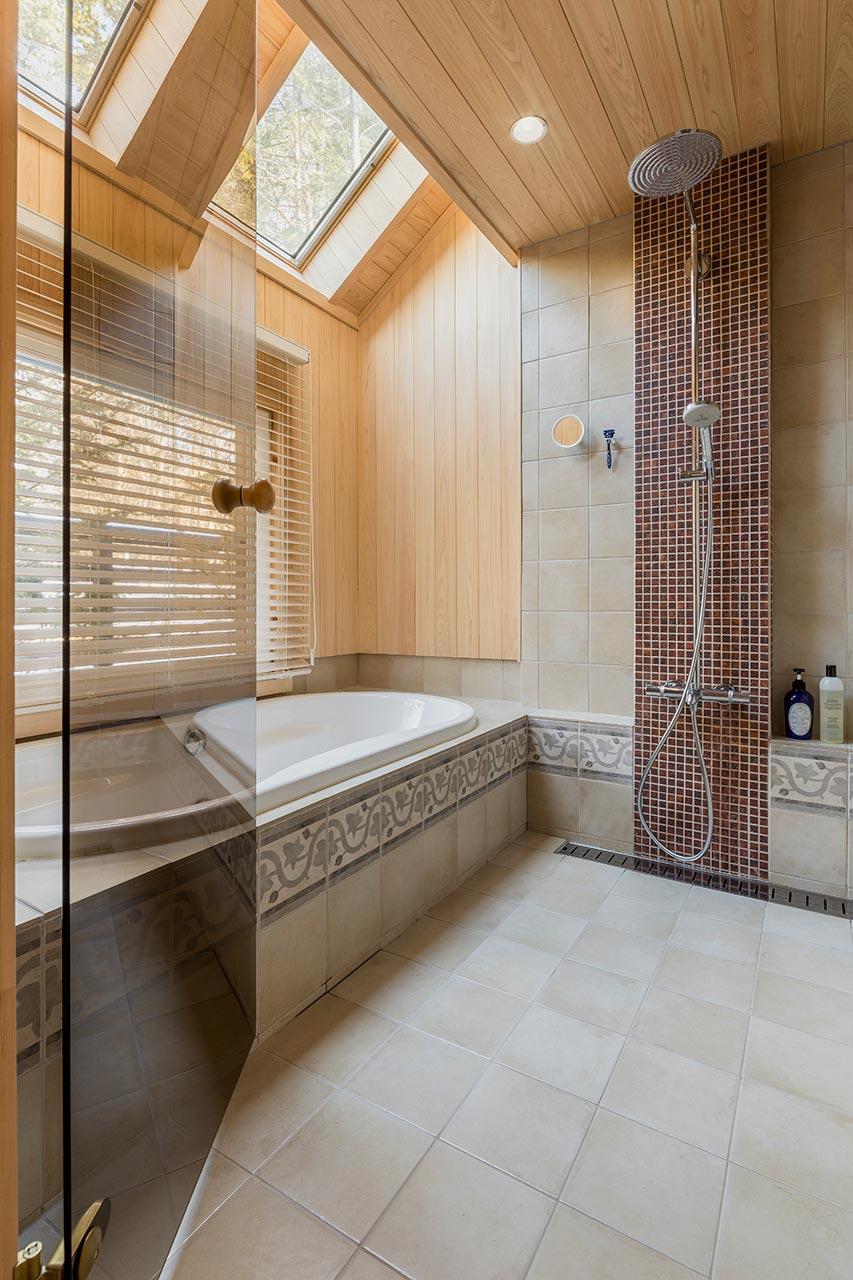 大きな窓と天窓で、角度の違う光が入る明るいバスルーム