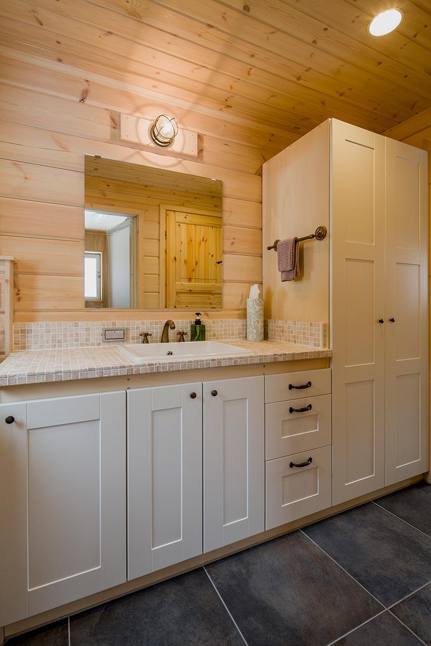やわらかな色味のタイルの洗面台は、木の壁と調和しています。