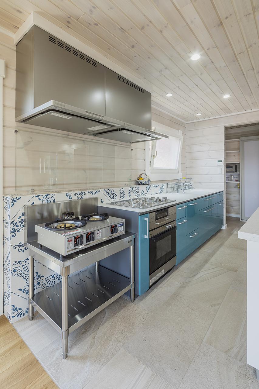 部屋のアクセントにもなっているスカイブルーのキッチン。床はお手入れのしやすいタイル張り。